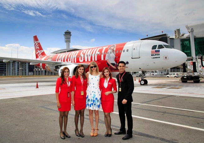Taylor Swift posing in front of Air Asia plane red tour