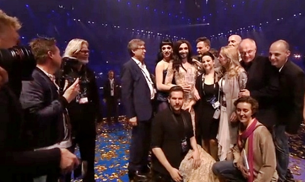conchita wurst and team on stage after winning eurovision song contest